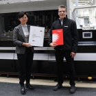 Yuan Li, responsible for pre-press technology at the Fogra Research Institute for Media Technologies, presents the Fogra certificate to Canon Production Printing's color consultant, Jochen Schäffner