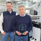 Retriever Sports' managing director Ian Bennett with an award presented by Mark Andy's Phil Baldwin (center) to commemorate the first Evolution Series E5 to be installed in the UK – with them is graphic designer Colin Raynsford