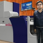 Akshat Jain, director of Bahubali Digiglam in the front of newly installed Konica Minolta MGI Jetvarnish 3D One