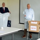 Mondi employees Alfons Kruse (second from right) and Detlef Stöppelmann (right) hand over the first 500 garments