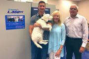Chase Lehigh, digital specialist, Jan Lehigh, president, and Bob Peretic, print products manager, with Alpine's digital press and Scubby, the office mascot