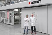 L-R: Alessandro Marino, technical Director, AMB; Alberto Vaglio Laurin, business director Italia, Bobst Italia, in front of the Expert CI flexo press in AMB production plant in San Daniele del Friuli, Italy