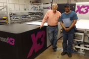 Mark Turk, left, president and CEO, and Alvin Page, inkjet press operator, alongside the Inca OnsetX3 with three-quarter automation at International Label, Elk Grove Village, Illinois.