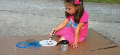 Vicki Strull's daughter, Eden, reusing an empty furniture box as a canvas