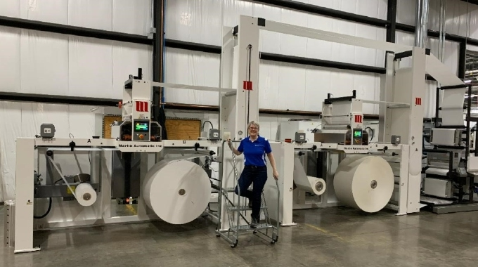 Sally Sann, label production manager, displays two Martin Automatic butt splicers installed in Wisconsin