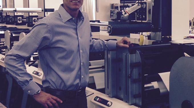 Tom Cummings, president and founder of Primeflex Labels, with the company's FB-3, its firat Nilpeter press, which was installed in March